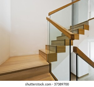 contemporary stair case with wooden steps and glass rails