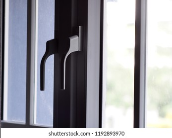 contemporary style door and windows opener grip on aluminium metal glass window frame inner side of a hostel room selective focus blur urban environment background outside