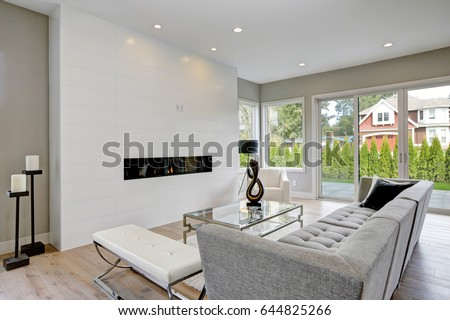 Contemporary Style Living Room With Modern Gas Fireplace Wood Flooring And Glass Doors Surrounded By