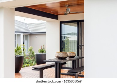 A contemporary style Patio with a stylish black snack counter and benches and two black high flower pots.