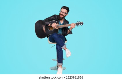 Contemporary stylish man with beard sitting on chair with guitar showing rock-and-roll gesture at camera