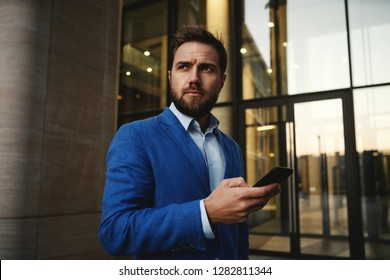 Contemporary stylish man wearing suit and using cellphone on street with background of modern building looking away
