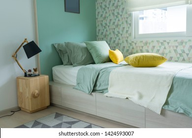 Contemporary teen bedroom with green pillow and modern side table lamp.