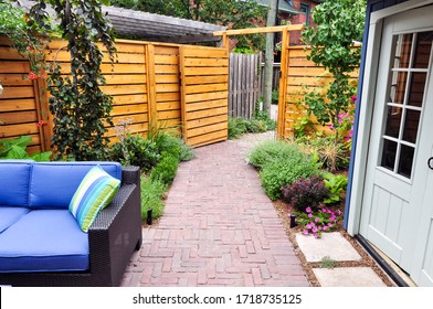 Contemporary with traditional elements, this beautiful small urban backyard garden features a seat wall, red brick paver herringbone pattern patio, natural stone steps and relaxing furniture.