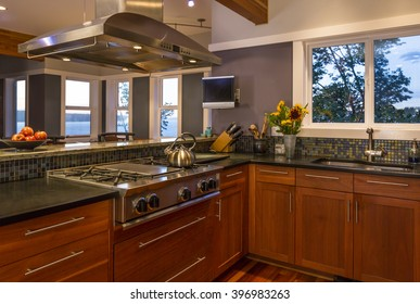 Contemporary upscale home kitchen interior with wood cabinets, gas stove, stainless steel vent hood, concrete countertops, glass tile backsplash and view windows