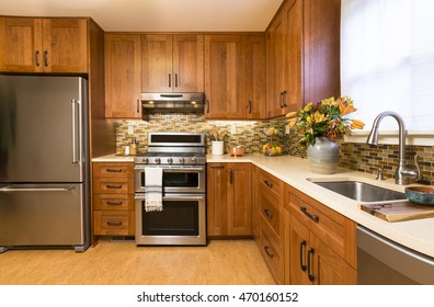 Contemporary upscale home kitchen interior with cherry wood cabinets, quartz countertops, sustainable recycled linoleum floors & stainless steel appliances including refrigerator & gas stove