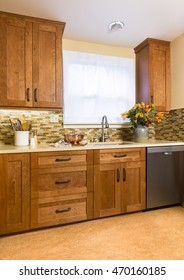 Contemporary upscale home kitchen interior with cherry wood cabinets, quartz countertops, sustainable recycled linoleum floors and stainless steel appliances