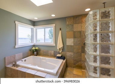 Contemporary upscale home spa bathroom interior with glass tile shower, slate tile walls, acrylic soaking tub and view windows