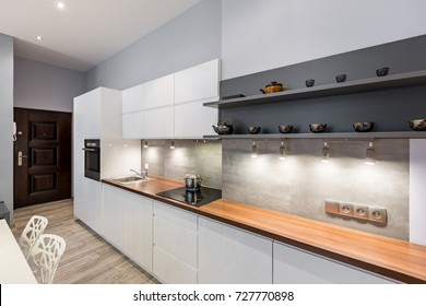 Contemporary white kitchen with wooden countertop and led lighting