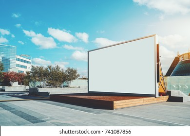 Contemporary wooden stage in urban settings with blank information LCD screen or banner; empty mock-up of poster; white clean billboard with copy space zone for logo, text or advertising caption