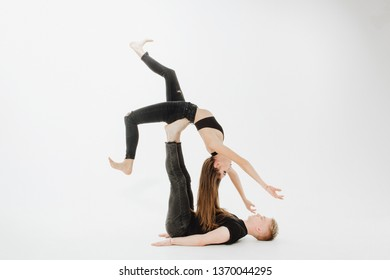 Contemporary Young Couple Dance Lift on Low Level. Blond Male Dancer Hold Girl with Allonge Hand and Flex Foot Upside Down. Muscular Acrobat Perfomer in Black Isolated on White Background