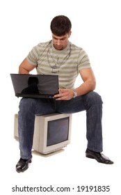 contemporary young guy sitting on an old-fashioned computer and working with laptop, isolated on white background