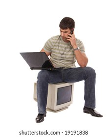 contemporary young guy sitting on an old-fashioned computer, working with laptop and talking over a mobile phone, isolated on white background