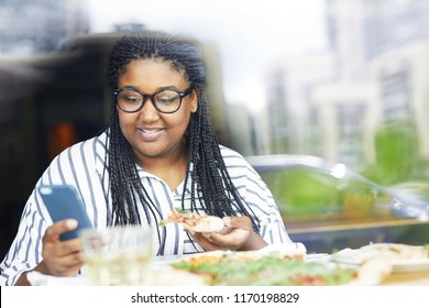 Contemporary young woman with smartphone and slice of pizza texting by lunch in cafe