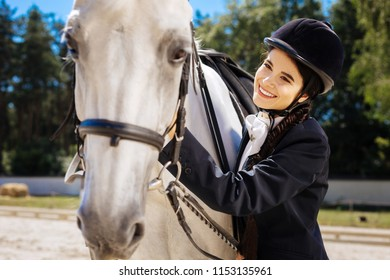 Contended horsewoman. Dark-eyed horsewoman with long braid feeling contended after nice horse racing