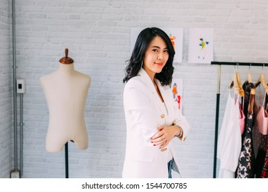 Content Asian fashion designer standing at table and having arms crossed with sewing equipment and smiling at camera in light workshop