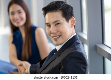 Content Asian male and female entrepreneurs sitting in office and shaking hands during business meeting and looking at each other