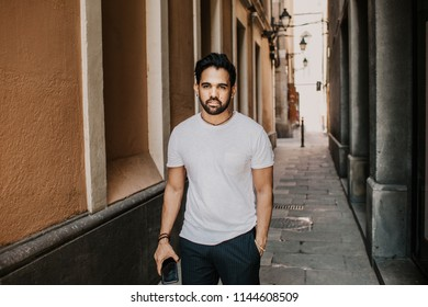 Content attractive hispanic man in white tshirt walking old town streets holding mobile phone hand.Bearded hipster male enjoying city travel on gotic district streets