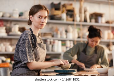Content attractive young craftswoman in apron sitting at table and adjusting small bowl while processing clay crockery in workshop