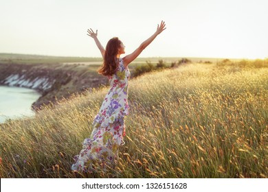 Content brunette in long summer dress standing in high grass with arms raised facing sunlight