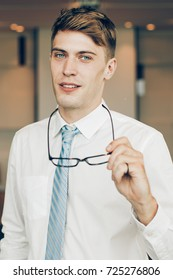 Content Business Man Taking off Glasses in Office