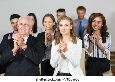 Content business people applauding to speaker after lecture