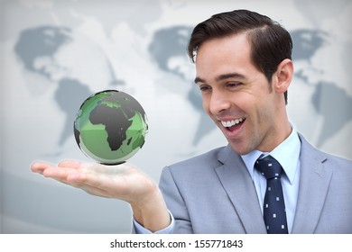 Content businessman admiring a green globe on map background