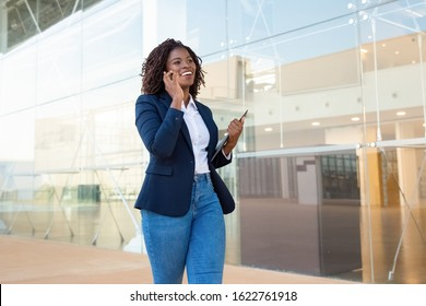 Content businesswoman walking and talking by smartphone. Cheerful young African American businesswoman talking by cell phone and looking away. Communication concept