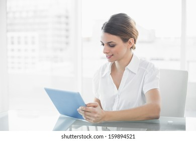 Content businesswoman working with her tablet sitting at her desk