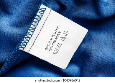 Content and care clothes label on blue textile background closeup