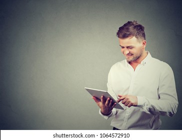 Content casual guy in white shirt browsing modern tablet enjoying new device standing on gray.