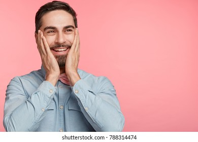 Content cheerful male feels shy and embarrasment, keeps hands on cheeks as rouges, recieves compliment about his appearance and look, expresses positive emotions, isolated over pink background