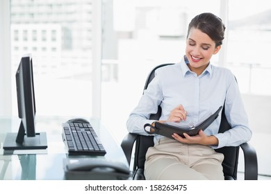 Content classy brown haired businesswoman checking her agenda in bright office