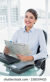 Content classy brown haired businesswoman reading a newspaper in bright office