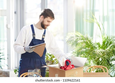 Content confident bearded moving company employee unpacking box with decoration stuff and making notes about goods in sketchpad