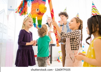 Content confident girl in party hat standing at colorful horse pinata and hitting cit with bat at kids celebration, parents playing with children