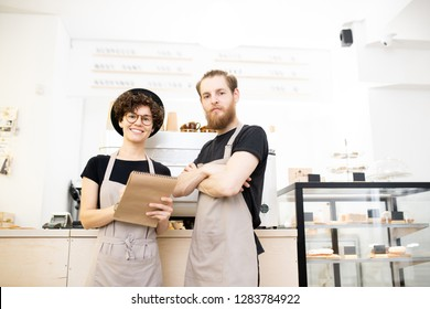 Content confident team of coffee shop: smiling young man and woman in aprons standing at counter and looking at camera while analyzing notes in sketchpad