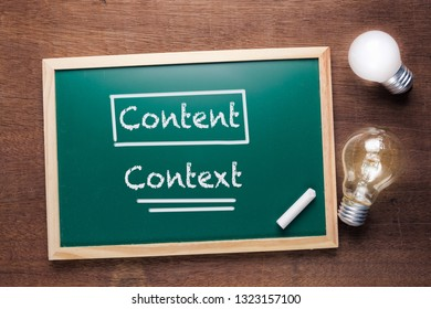 Content and Context on chalkboard with two glowing light bulbs, content marketing concept