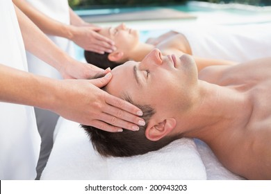 Content couple enjoying head massages poolside outside at the spa
