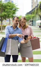 Content couple of shoppers getting cash back for purchases