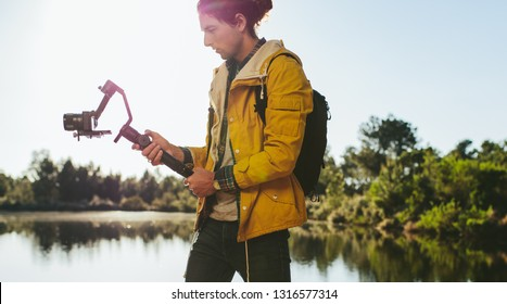 Content creator shooting a video using a mirrorless camera mounted on a hand held gimbal. Side view of a traveler looking at his digital camera to take a photo standing beside a lake.