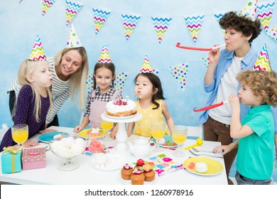 Content cute girls in colorful party hats standing at table with desserts and blowing out candles on cake, mother and boy blowing our party horns