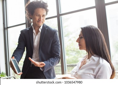 Content enterprising Asian man showing survey results on tablet while sharing business strategy. Smiling confident businessman presenting report to colleague in office. Technology concept