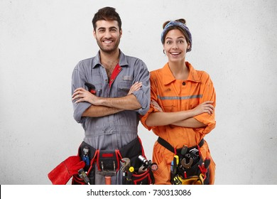 Content female and male technicians in special uniform keep hands folded as wait for instruction from work superintendent or foreman, have smiles as being yet not tired, full of energy and strength