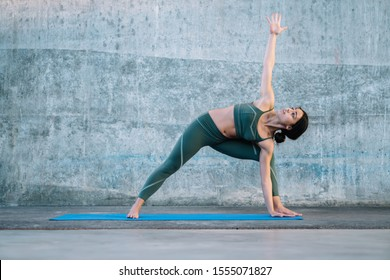 Content fit active female in sports outfit showing revolved warrior with extended arms posture standing on yoga mat on concrete background outdoors