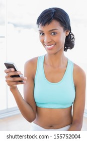 Content fit woman texting with her mobile phone in a living room