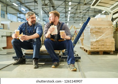 Content handsome bearded colleagues in workwear sitting on pallet jack and drinking coffee while eating buns in factory shop
