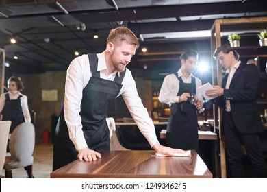 Content handsome young bearded waiter  in black apron wiping table with cloth in restaurant while manager showing seating chart to waiter in background