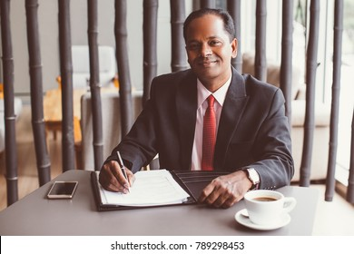 Content Indian Businessman Completing Form in Cafe