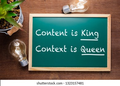 Content is King, Context is Queen : text on chalkboard with glowing light bulbs on wood table background